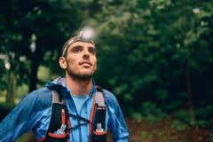Het geschikte mannetje jogger met een koplamp rust tijdens opleiding voor dwars de sleepras van het land in aardpark royalty-vrije stock afbeeldingen