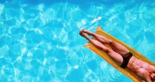 Het geschikte mens ontspannen op lilo in zwembad stock videobeelden