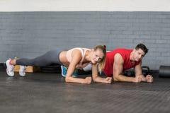 Het geschikte paar planking samen in gymnastiek royalty-vrije stock afbeelding