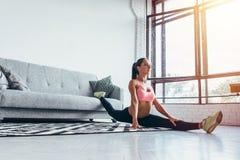Het geschikte vrouw gespleten doen thuis uitoefenend Flexibiliteit, het uitrekken zich, geschiktheid Stock Foto