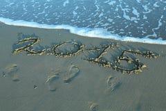 Het geschreven jaar van 2015 in het zand van het overzees Stock Foto's