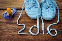 het geschreven kant van 2016 jaar van kinderschoenen en een fopspeen Royalty-vrije Stock Foto