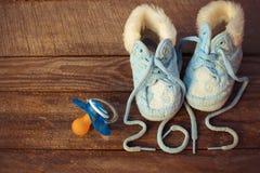 het geschreven kant van 2015 jaar van kinderschoenen en een fopspeen op de oude houten achtergrond Stock Afbeeldingen