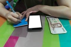 Het gesloten omhoog vrouw schrijven op de notastootkussen van de lijmstok met ziet slimme ph royalty-vrije stock foto's