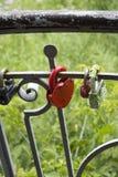 Het gesloten rode oude slot hangen op de omheining Stock Foto