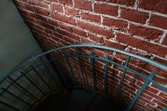 Het gesmede ijzer verdraaide treden met bezinning over een rode bakstenen muur, leuningen van het oude uitstekende gebouw, art. Stock Foto
