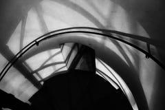 Het gesmede ijzer verdraaide treden met bezinning over een rode bakstenen muur, zwart-witte leuningen van het oude uitstekende ge Stock Afbeeldingen
