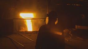 Het gesmolten hete staal gieten en arbeiders stock video