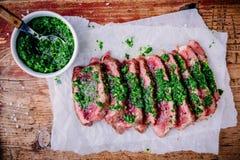 Het gesneden geroosterde lapje vlees van het barbecuerundvlees met groene chimichurrisaus stock foto's