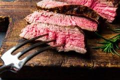 Het gesneden geroosterde middelgrote zeldzame rundvleeslapje vlees diende op houten raadsbarbecue, bbq het haasbiefstuk van het v royalty-vrije stock foto