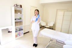 Het gespecialiseerde schoonheidsspecialistmeisje treft voor begin van werkend DA voorbereidingen Stock Foto