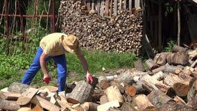 Het gespleten logboek van de landbouwersmens met de werf van het bijldorp dichtbij houten stapel 4K stock footage