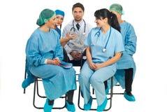 Het gesprek van artsen op stoelen Stock Foto's