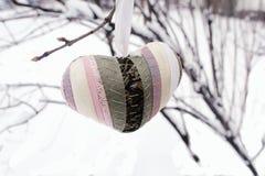 Het gestreepte hart van Valentine op een snow-covered tak De ruimte van het exemplaar stock afbeelding