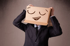 Het gesturing van de zakenman met een kartondoos op zijn hoofd met smil Stock Foto