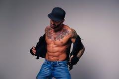 Het getatoeeerde mannetje kleedde in jeans, GLB en vest op naakt t stock afbeelding