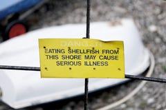 Het gevaar dat schaaldieren eet kan ernstig ziektewaarschuwingsbord bij strand veroorzaken stock fotografie