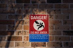 Het gevaar, gaat teken en geen symbool op bakstenen muur in stock fotografie
