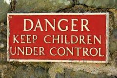 Het gevaar houdt kinderen onder controleteken Stock Foto's