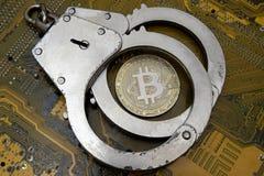 Het gevaar van computerfraude, hakkeraanvallen of schending van de wet in het crypto-munt gebied Bitcoin ligt onder politiestee royalty-vrije stock afbeeldingen