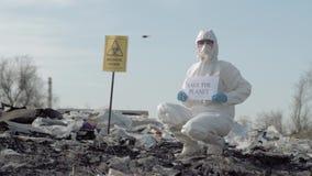 Het gevaarlijke gebied, Hazmat-wetenschapper in beschermend kostuum toont teken sparen de planeet op troepyard met biologische wi stock footage