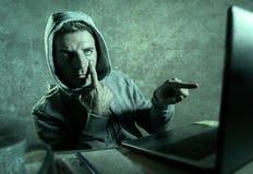 Het gevaarlijke kijken hakkermens die in hoodie het computersysteem die van Internet binnendringen in een beveiligd computersyste stock afbeelding