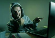 Het gevaarlijke kijken hakkermens die in hoodie het computersysteem die van Internet binnendringen in een beveiligd computersyste stock foto