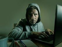 Het gevaarlijke kijken jonge hakkermens in hoodie het typen op mede laptop royalty-vrije stock fotografie