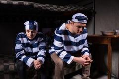 Het gevangenepaar die eenvormige gevangenis dragen heeft in gedachten binnen verloren Royalty-vrije Stock Foto's