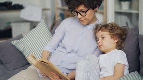 Het geven het boek van de mammalezing aan weinig zitting van de kind leuke krullende jongen op bank in ruimte stock videobeelden