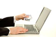 Het geven van contant geld aan de computer Stock Fotografie