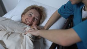 Het geven verpleegster het vertellen grappen die aan oude vrouwelijke patiënt in ziekbedrehabilitatie liggen stock video
