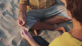 Het gewas van hoger paar zit en samen mediterend op zandig strand stock footage