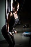 Het Gewichtheffen van de vrouw bij Gymnastiek Het uitoefenen op trekkracht onderaan gewichtsmachine Vrouw die trekkracht-UPS doen royalty-vrije stock afbeelding