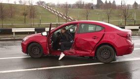 Het gewonde meisje zit in een gebroken auto na een autoongeval op een natte weg stock footage