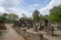 Het gezette die standbeeld van Boedha door een bakstenen muur in het Historische Park van Sukhothai wordt omringd stock foto's