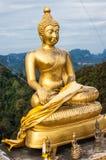 Het gezette gouden standbeeld van Boedha op heuveltop Royalty-vrije Stock Fotografie