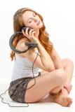 Het gezette meisje overweegt over audio Stock Fotografie