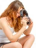 Het gezette meisje overweegt over audio Stock Afbeeldingen