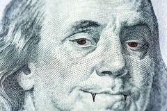 Het gezicht van Benjamin Franklin met rode ogen en hoektanden zoals een vampier, een symbool die van een bloedzuiger, uit geld, i royalty-vrije illustratie
