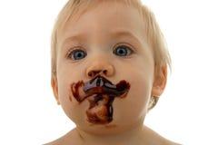 Het gezicht van de baby met chocolade Stock Foto's
