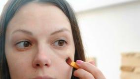 Het gezicht van de close-upvrouw ` s De vrouw zet een Stichtings toon- room op het gezicht gebruikend een borstel voor de spiegel stock video