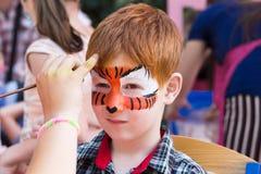 Het gezicht van de kindjongen schilderen, die het proces van tijgerogen maken Stock Foto