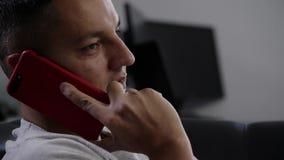 Het gezicht van de leuke donkerbruine mens in grijze t-shirt spreekt op smartphone leggend op bank stock footage
