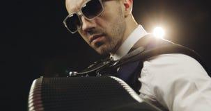 Het gezicht van de musicus in zonnebril op een helder achterlicht stock video