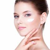 Het gezicht van de schoonheid van jonge vrouw met kosmetische room op een wang stock fotografie