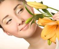 Het gezicht van de vrouw met gele leliebloem stock afbeelding