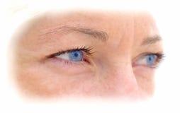 Het gezicht van de vrouw met kleurrijke blauwe ogen. Stock Afbeelding