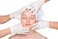 Het gezicht van de vrouw in rubberhanden van artsen Royalty-vrije Stock Afbeeldingen