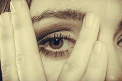 Het gezicht van de vrouwendekking kijkt door vingers Royalty-vrije Stock Foto's